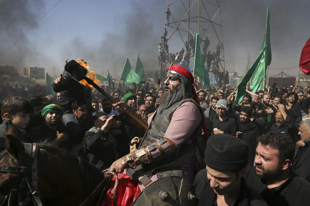 A Shiite re-enacts the events of Ashoura while Iranian and Iraqi Shiite Muslims mourn in a procession in southern Tehran, Iran, Oct. 12, 2016. Shiites mark Ashoura, the tenth day of the Muslim month of Muharram, to commemorate the martyrdom of Imam Hussein, a grandson of the Prophet Muhammad and one of Shiite Islam's most beloved holy people, during the 7th century Battle of Karbala in present-day Iraq.