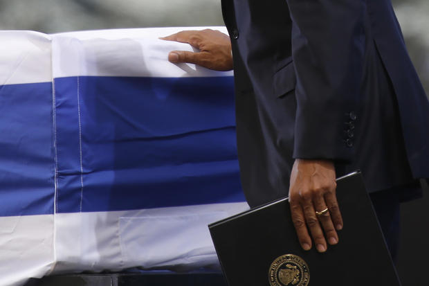 President Obama touches the flag-draped coffin of former Israeli President Shimon Peres during his funeral at the Mount Herzel national cemetery in Jerusalem, Sept. 30, 2016.