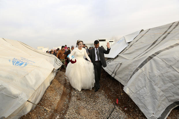 Iraqi internally displaced groom Jassim Mohammed walks with his bride, Amena Ali, during their wedding ceremony at a camp for internally displaced people, in Khazir, near Mosul, Iraq, Dec. 8, 2016.