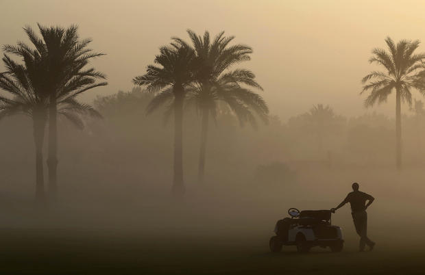 A marshal looks through the early morning fog which delayed the 1st round of the Dubai Ladies Masters golf tournament in Dubai, United Arab Emirates, Dec. 7, 2016.