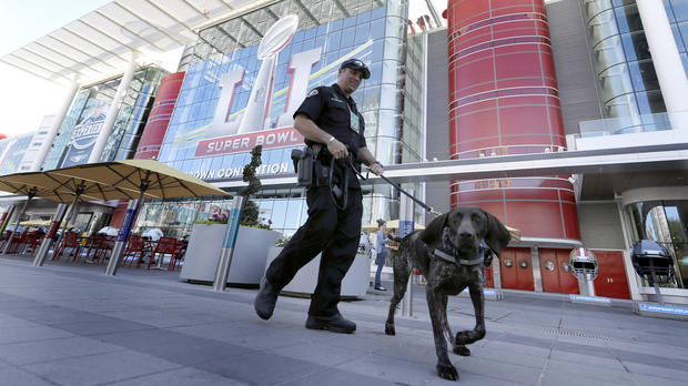 Officer Keith McCart, of the Long Beach, Calif., Police Department, patrols with K-9 Pidura outside the George R. Brown Convention Center, the NFL Super Bowl 51 football media center and site of the NFL Experience, Jan. 31, 2017, in Houston.