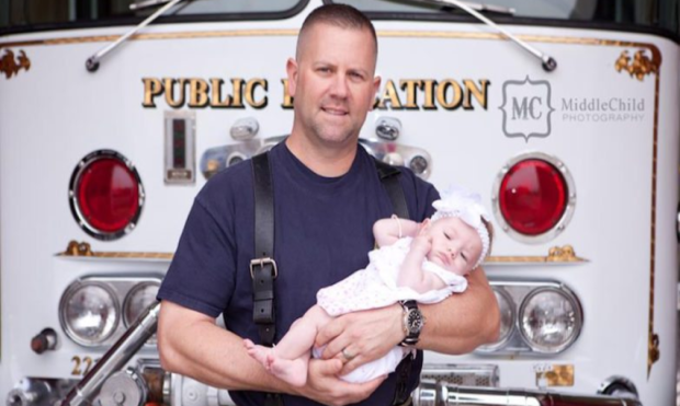 Marc Hadden poses with his newborn daughter, Gracie, shortly after her adoption.