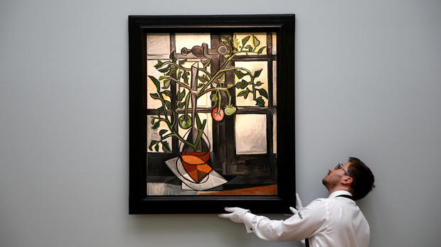 """A worker poses with Pablo Picasso's """"Plant de tomates"""" ahead of an upcoming sale at Sotheby's auction house in London, Britain, Feb. 22, 2017."""