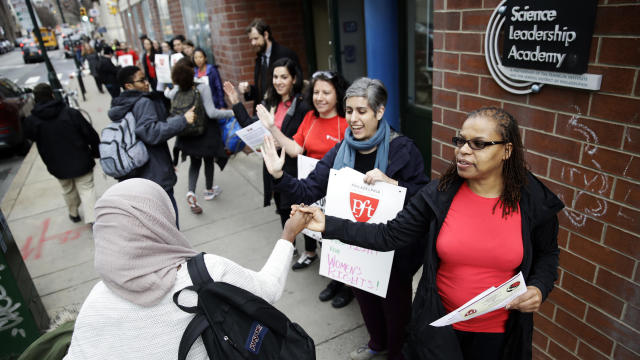 """Teacher Pia Martin greets students as they arrive to school at the Science Leadership Academy as teachers take part in a """"A Day Without a Woman"""" demonstration in Philadelphia March 8, 2017."""
