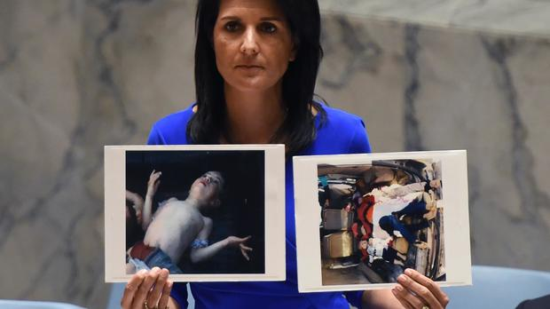 U.S. Ambassador to the U.N. Nikki Haley holds photos of victims as she speaks as the U.N. Security Council meets in an emergency session at the U.N. on April 5, 2017.