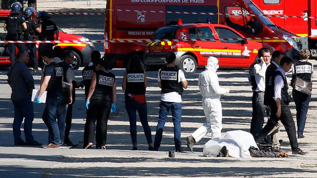 Police inspect the body of a suspect at the scene of an incident in which a car rammed a gendarmerie van on the Champs-Elysees in Paris, France, June 19, 2017.