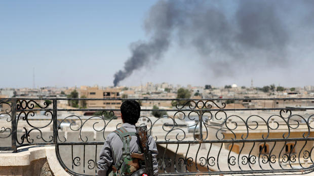 A Kurdish fighter from the People's Protection Units looks at a pillar of smoke after a coalition airstrike in Raqqa, Syria, June 16, 2017.