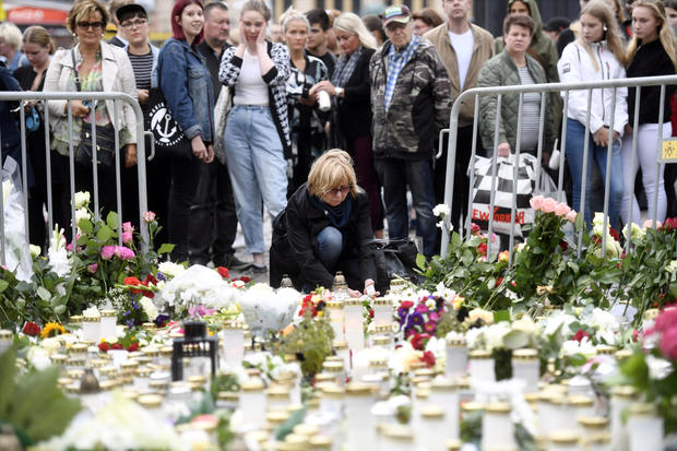 Mourners bring memorial candles and flowers to the Turku Market Square