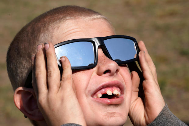Cooper Jackson tries out his new solar glasses in a designated eclipse viewing area in a campground near Guernsey