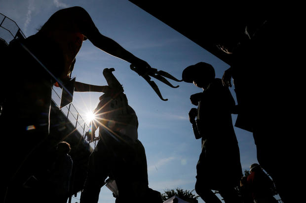 A worker passes out solar viewing glasses to guests at the football stadium to watch the total solar eclipse at Southern Illinois University in Carbondale