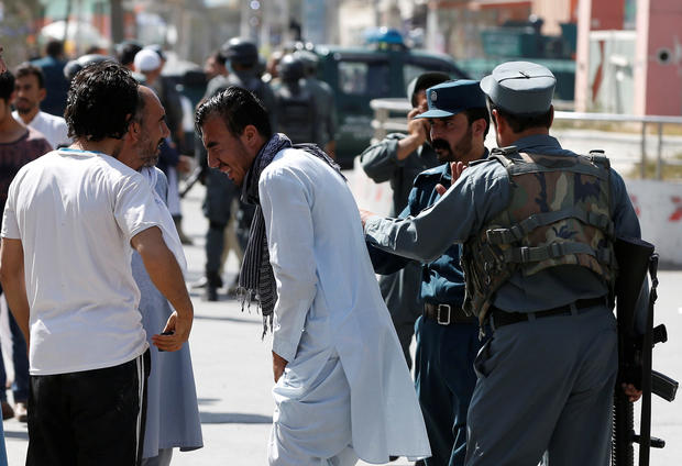 Afghan policemen try to comfort a man whose relatives were stuck at the site of a suicide attack followed by a clash between Afghan forces and insurgents after an attack on a Shi'ite Muslim mosque in Kabul