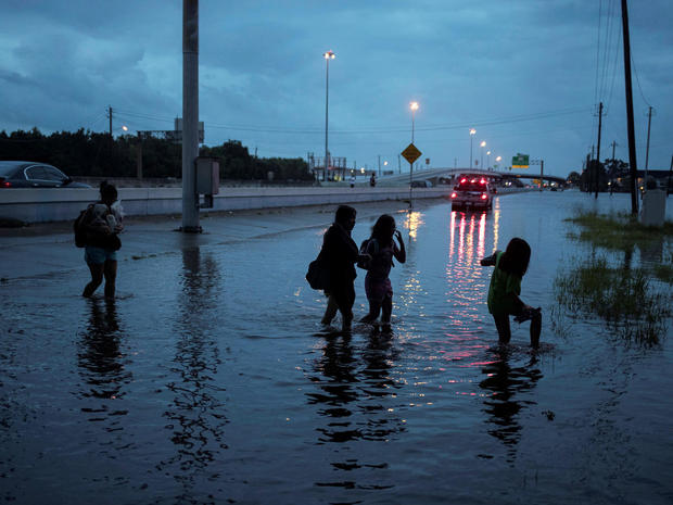 Members of the Duong family walk through flood waters from Tropical Storm Harvey in Houston, Texas