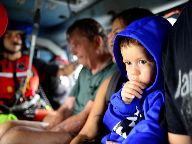 Evacuees are airlifted in a U.S. Coast Guard helicopter after flooding due to Hurricane Harvey inundated neighborhoods in Houston