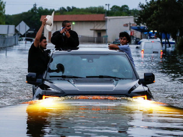 Residents use a truck to navigate through flood waters from Tropical Storm Harvey in Houston, Texas,