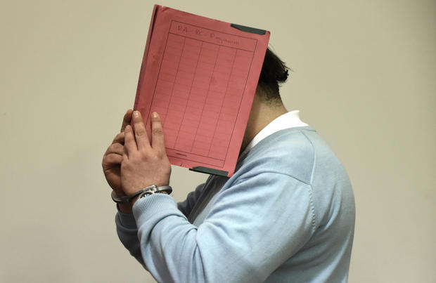 Former nurse Niels H. masks his face with a folder on his arrival in the courtroom in Oldenburg