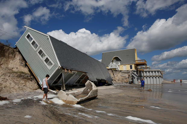 Local residents look at a collapsed coastal house after Hurricane Irma passed the area in Vilano Beach