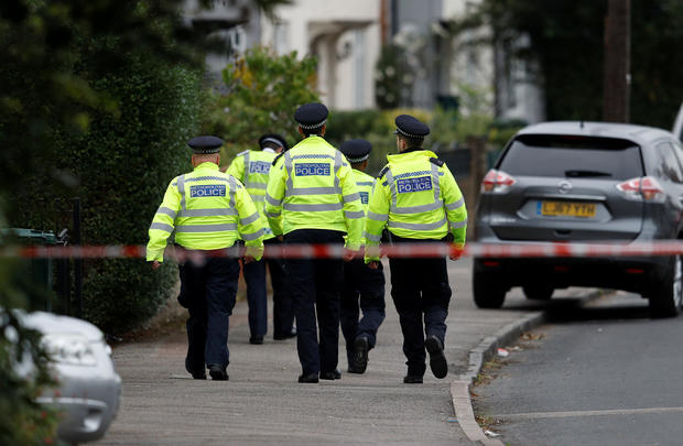 Police officers walk behind cordon tape set up around a property being searched after a man was arrested in connection with an explosion on a London Underground train, in Sunbury-on-Thames