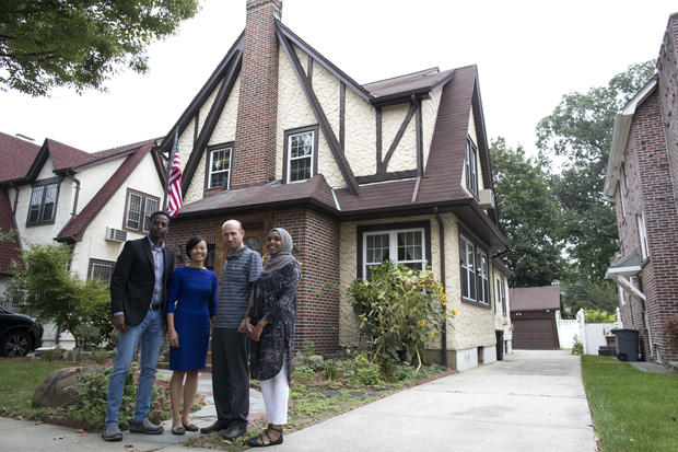 Abdi Iftin, left, of Somalia; Uyen Nguyen, second from left, of Vietnam; Eiman Ali, right, of Somalia but born in Yemen; and Ghassan al-Chahada of Syria pose for a photo outside President Trump's boyhood home in the Jamaica Estates neighborhood of the Que