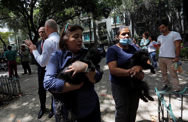 Women carrying their dogs stand outside their homes after an earthquake in Mexico City