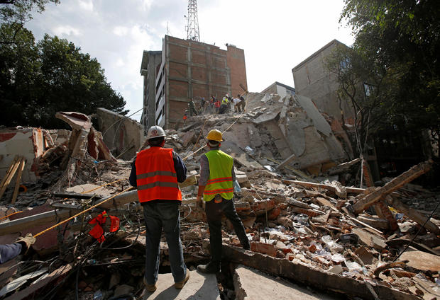 Rescue workers look at fellow workers searching for people under the rubble of a collapsed building after an earthquake hit Mexico City, Mexico