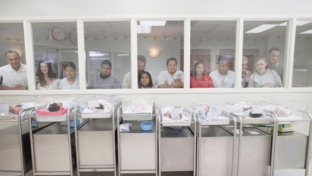 New parents watching babies in hospital nursery