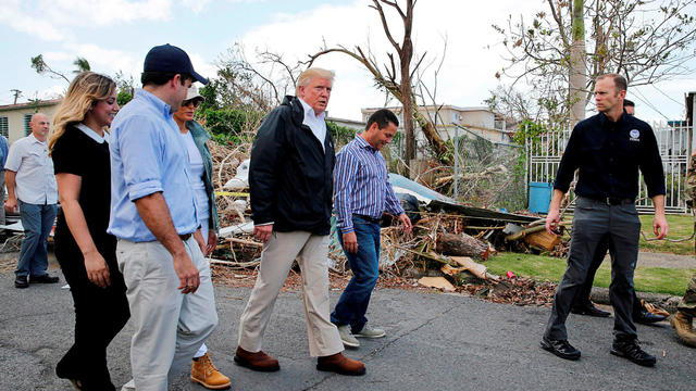 President Trump walks past hurricane wreckage as he visits areas damaged by Hurricane Maria in Guaynabo, Puerto Rico