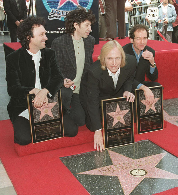 Musician Tom Petty (3rd-L) touches the star he and