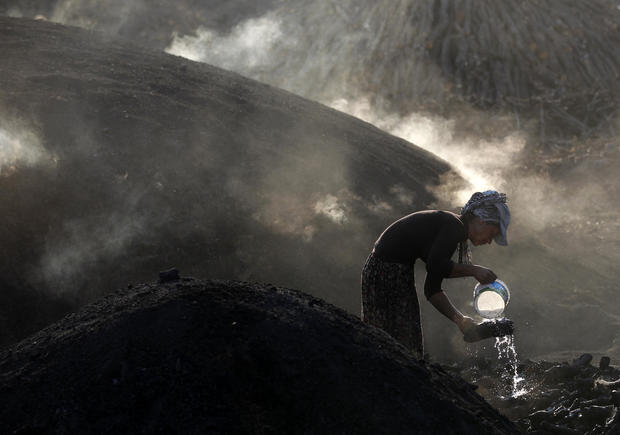 A woman sprays water on burning woods during a charcoal making process near Kizilcahamam