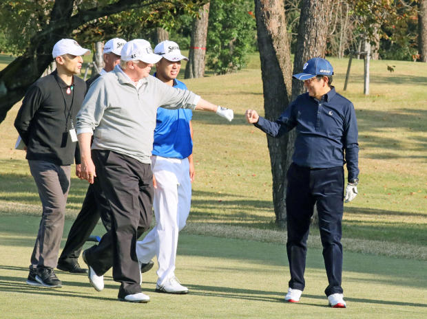 U.S. President Donald Trump gestures to Japan's Prime Minister Shinzo Abe as Japanese professional golfer Hideki Matsuyama looks on, as they play golf at the Kasumigaseki Country Club in Kawagoe, Japan