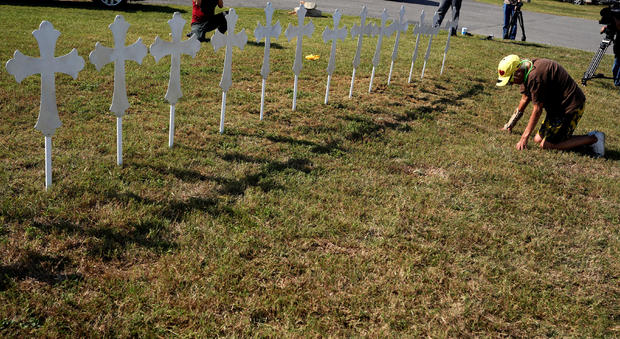 Brandy Jones prays in front of 26 crosses erected near the site of the shooting at the First Baptist Church of Sutherland