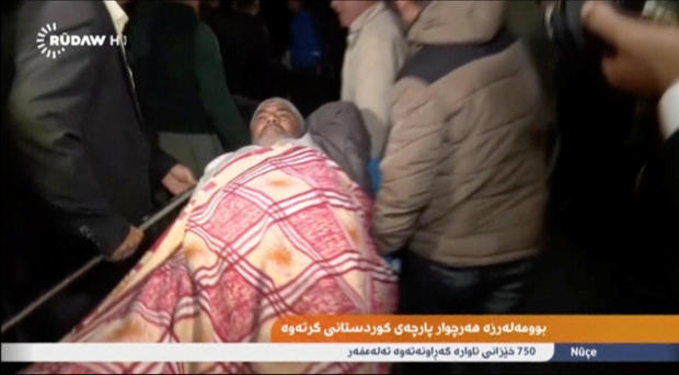 An injured man lies on a stretcher as he is taken to hospital after an earthquake at an unknown location in Iraq