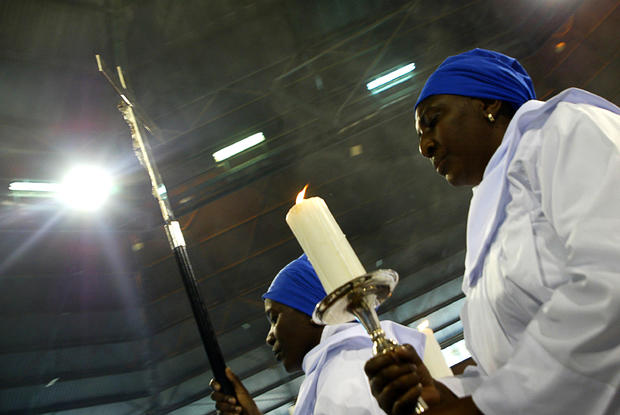 Two women hold a candle and a cross as t