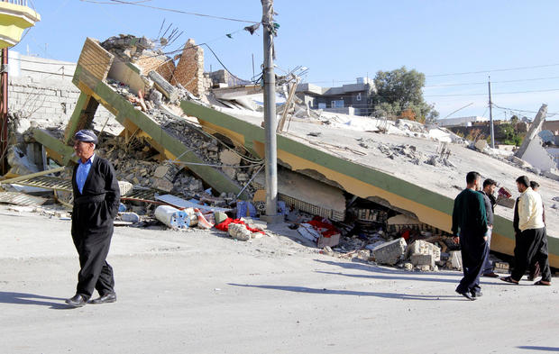 People walk past a damaged building following an earthquake in the town of Darbandikhan