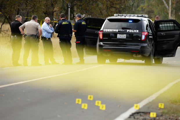 Law enforcement officers and investigators converse near a police vehicle that was involved in a shooting on Nov. 14, 2017, in Rancho Tehama, California.