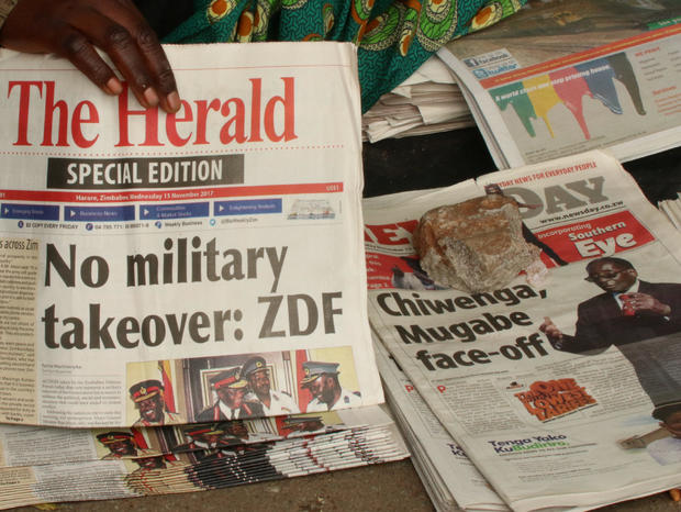 A vendor picks up a copy of a special edition of the state-owned daily newspaper The Herald in Harare