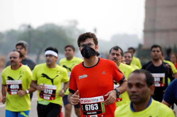 A runner wearing a face mask takes part in the Airtel Delhi Half Marathon in New Delhi
