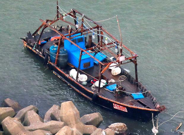A wooden boat is seen near a breakwater in Yurihonjo