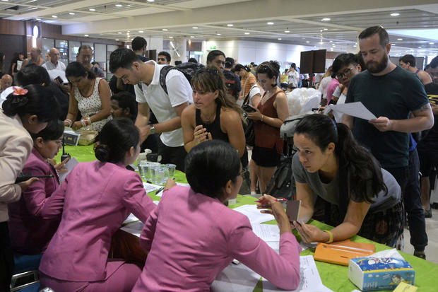 Passengers ask staff about their flights after Ngurah Rai airport closed their operation due to eruption of Mount Agung in Bali resort island