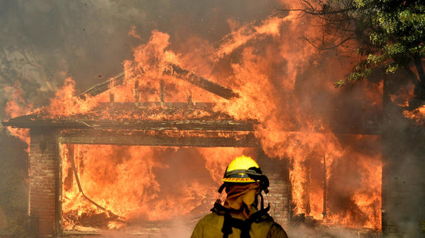 Firefighters battle to save one of many homes burning in the so-called Creek Fire that broke out in the Kagel Canyon area in the San Fernando Valley north of Los Angeles, in Sylmar, California, Dec. 5, 2017.