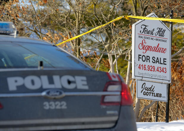 A police vehicle is parked outside the home of billionaire founder of Canadian pharmaceutical firm Apotex Inc. in Toronto