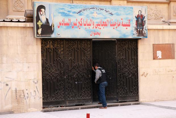 An Egyptian security member inspects the entrance gate of a church south of the capital Cairo following a gun attack on Dec. 29, 2017.