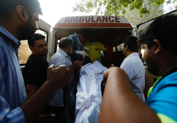 Family members carry the body of victim killed in a fire at a restaurant from a hospital in Mumbai