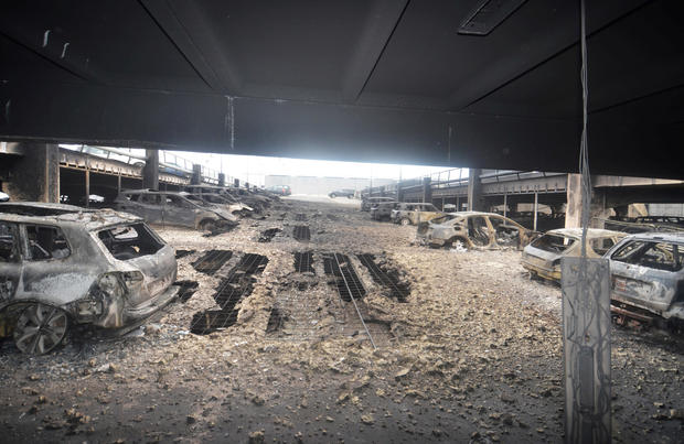 Burnt cars are seen in what remains of the multi-storey car park, where a large fire destroyed many cars on Sunday, in King's Dock, Liverpool