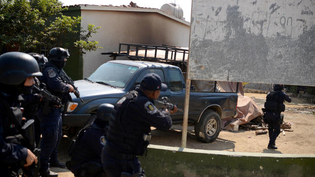 Police officers arrive near where an exchange of gunfire took place between residents and members of a local, self-appointed community police force which according to local media, left 11 dead in La Concepcion