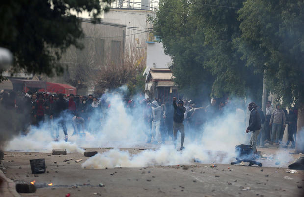 Tear gas is seen as protesters clash with riot police attempting to disperse the crowd during demonstrations against rising prices and tax increases, in Tebourba