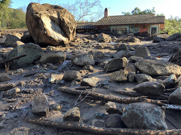 A damaged house is surrounded by large boulders and debris following mudslides due to heavy rains in Montecito