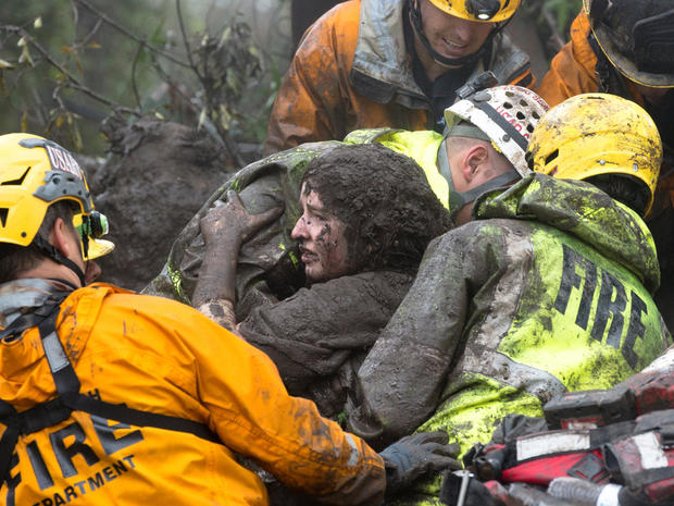 Emergency personnel carry a woman rescued from a collapsed house after a mudslide in Montecito