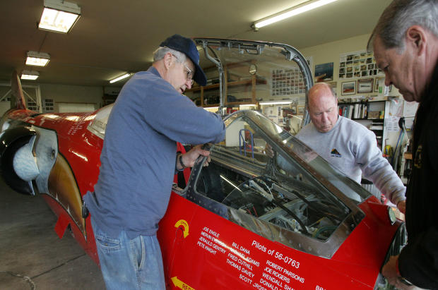 From left, Von Armstrong, Richard Pengelley and Ed Shadle set the windshield down onto the front of the North American Eagle jet-powered vehicle May 3, 2008, in Spanaway, Wash. A handful of Snohomish County residents are part of a team of airplane mechani