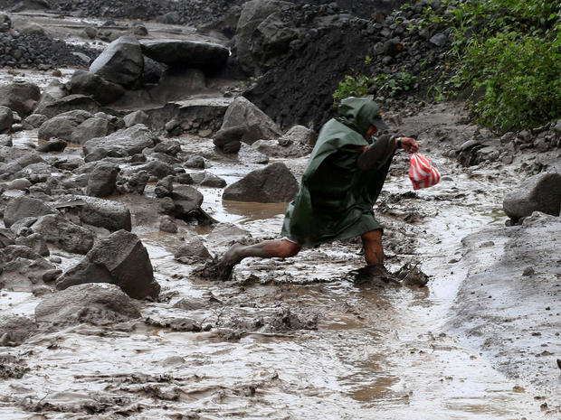 A resident wades through a river with lahar flow coming from Mount Mayon volcano in Guinobatan, Albay province, south of Manila