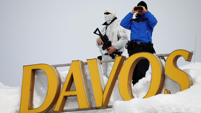 Swiss police officers observe the surrounding area from atop the roof of the Davos Congress Hotel during the World Economic Forum (WEF) annual meeting in Davos